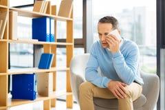 Trauriger schwermütiger Mann, der ein Papiergewebe hält Stockbild
