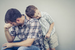 Trauriger Sohn, der seinen Vati nahe Wand umarmt lizenzfreie stockfotos