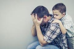 Trauriger Sohn, der seinen Vati nahe Wand umarmt Lizenzfreies Stockbild