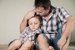 Trauriger Sohn und sein Vati, die auf dem Boden am Raum zur Tageszeit sitzt lizenzfreie stockbilder