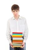 Trauriger Student, der Stapel der Bücher hält Stockfoto