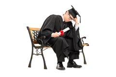 Trauriger Student im Aufbaustudium, der auf einer Holzbank sitzt Lizenzfreie Stockfotos