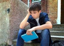 Trauriger Student mit einem Buch lizenzfreie stockbilder