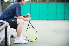 Trauriger Tennisspieler, der im Gericht nach sitzt, ein Match zu verlieren lizenzfreies stockbild