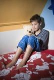 Trauriger und deprimierter Junge auf seinem Bett Lizenzfreie Stockfotografie