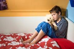 Trauriger und deprimierter Junge auf seinem Bett Stockfotografie