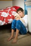 Trauriger und deprimierter Junge auf seinem Schlafzimmer Stockfotografie