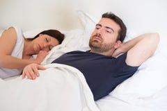 Trauriger und deprimierter Mann, der im Bett mit Frau liegt Lizenzfreie Stockbilder