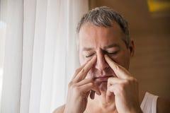 Trauriger und deprimierter Mann, der seinen Kopf mit seiner Hand, das Fenster bereitstehend hält Stockbild