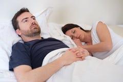 Trauriger und deprimierter Mann im Bett mit seiner Frau Stockbilder
