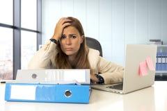 Trauriger und hoffnungsloser Geschäftsfrauleidendruck und -kopfschmerzen am Bürolaptopcomputertisch Stockfotos