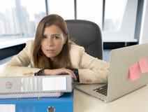 Trauriger und hoffnungsloser Geschäftsfrauleidendruck und -kopfschmerzen am Bürolaptopcomputertisch Stockfotografie
