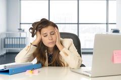 Trauriger und hoffnungsloser Geschäftsfrauleidendruck und -kopfschmerzen am Bürolaptopcomputertisch Lizenzfreie Stockfotografie