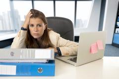 Trauriger und hoffnungsloser Geschäftsfrauleidendruck und -kopfschmerzen am Bürolaptopcomputertisch Stockbild