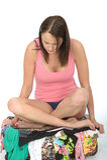 Trauriger unglücklicher Fed Up Young Woman Sitting auf einem überfließenden Koffer, der elend schaut Stockfotografie