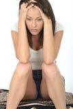 Trauriger unglücklicher Fed Up Young Woman Sitting auf einem Koffer, der elend schaut Lizenzfreies Stockfoto