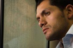 Trauriger widergespiegelter junger Mann depresed, grauer Hintergrund Lizenzfreies Stockbild