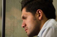 Trauriger widergespiegelter junger Mann depresed, grauer Hintergrund Lizenzfreies Stockfoto