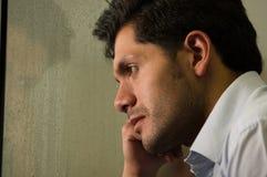 Trauriger widergespiegelter junger Mann depresed, grauer Hintergrund Lizenzfreie Stockfotos
