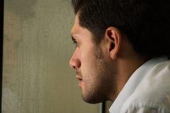 Trauriger widergespiegelter junger Mann depresed, grauer Hintergrund Stockfotografie
