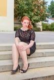 Trauriges überladenes Frauensitzen kleidete im Schwarzen auf einem Treppenhaus an Lizenzfreie Stockbilder