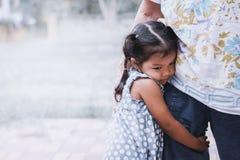Trauriges asiatisches kleines Mädchen, das ihr Mutterbein umarmt Stockbilder