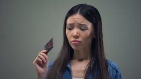 Trauriges asiatisches Mädchen, das über die süße Schokolade hält Diät, gesunde Nahrung träumt stock footage
