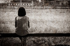 Trauriges asiatisches Mädchen, das alleine sitzt Stockbild