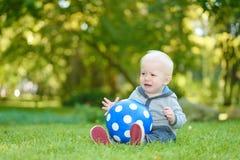 Trauriges Baby, das im grünen Gras sitzt Stockbilder
