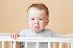 Trauriges Baby im weißen Bett stockfoto