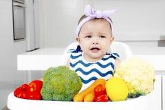 Trauriges Baby mit Gemüse in der Küche Stockbild