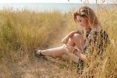 Trauriges blondes Mädchen, das auf Feld mit trockenem Gras sich entspannt Lizenzfreie Stockbilder