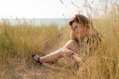 Trauriges blondes Mädchen, das auf Feld mit trockenem Gras sitzt Lizenzfreie Stockfotos