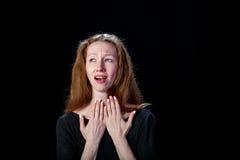 Trauriges Braunhaar des jungen Mädchens, das auf einem schwarzen Hintergrund schreit Stockbilder