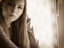 Trauriges deprimiertes jugendlich Mädchen, das auf Fensterbrett sitzt Stockbilder