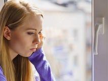 Trauriges deprimiertes jugendlich Mädchen, das auf Fensterbrett sitzt Stockfotografie