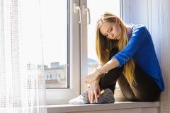 Trauriges deprimiertes jugendlich Mädchen, das auf Fensterbrett sitzt Lizenzfreies Stockbild