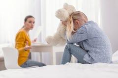 Trauriges deprimiertes Mädchen, das hinter Plüschbären sich versteckt Stockbild