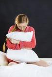Trauriges deprimiertes Mädchen in ergreifendem Kissen des Betts Stockfotografie