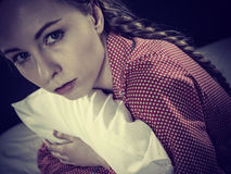 Trauriges deprimiertes Mädchen in ergreifendem Kissen des Betts Stockbilder