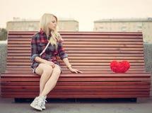 Trauriges einsames Mädchen, das nahe auf einer Bank zu einem großen roten Herzen sitzt Stockfoto