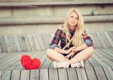 Trauriges einsames Mädchen, das nahe auf hölzernen Planken zu einem großen roten Herzen sitzt Lizenzfreies Stockfoto