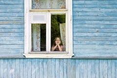 Trauriges gebohrtes kleines Mädchen, welches heraus das Landhausfenster lehnt ihr Gesicht auf ihren Händen schaut Stockfotografie