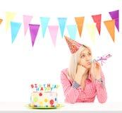 Trauriges Geburtstagsmädchen mit einem Kuchen lizenzfreies stockfoto
