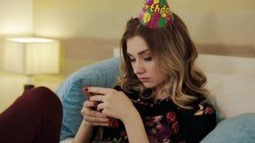 Trauriges Geburtstagsmädchen schreibt die Mitteilung auf Ihren Smartphone stock video