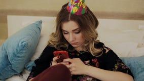 Trauriges Geburtstagsmädchen schreibt die Mitteilung auf Ihren Smartphone stock video footage