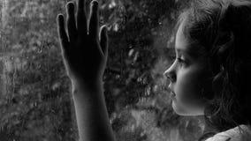 Trauriges gelocktes kleines Mädchen, welches heraus das Regentropfenfenster schaut stock video