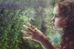 Trauriges gelocktes kleines Mädchen, welches heraus das Regentropfenfenster schaut stockfotografie