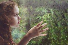 Trauriges gelocktes kleines Mädchen, welches heraus das Regentropfenfenster schaut stockbilder