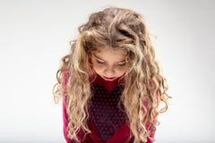 Trauriges gelocktes Schulmädchen mit Kopf unten Stockfoto